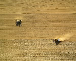 Cropfield with two tractors seen from above. Photo.