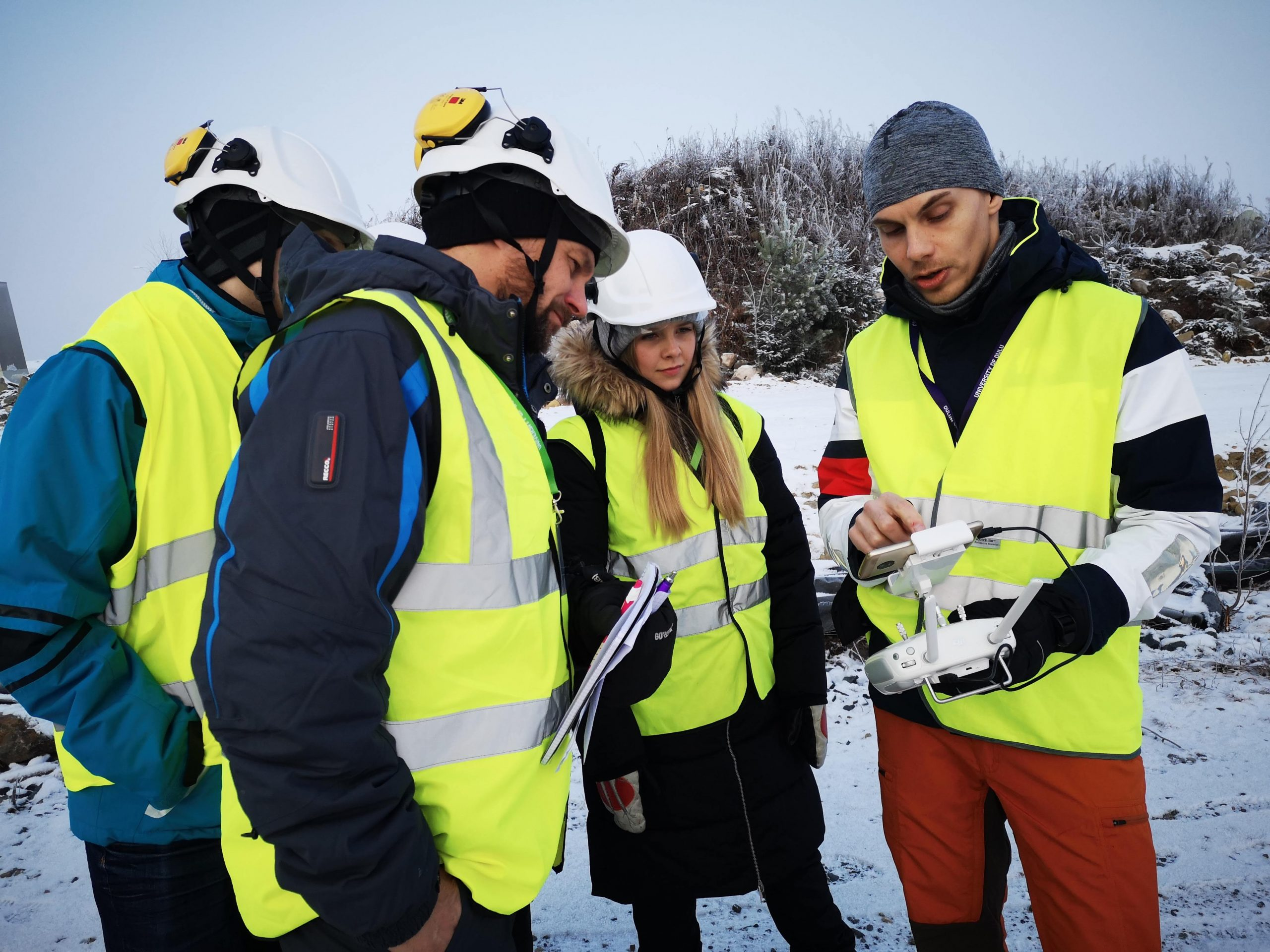 Four people in protection gear looking at a measuring instrument. Photo.